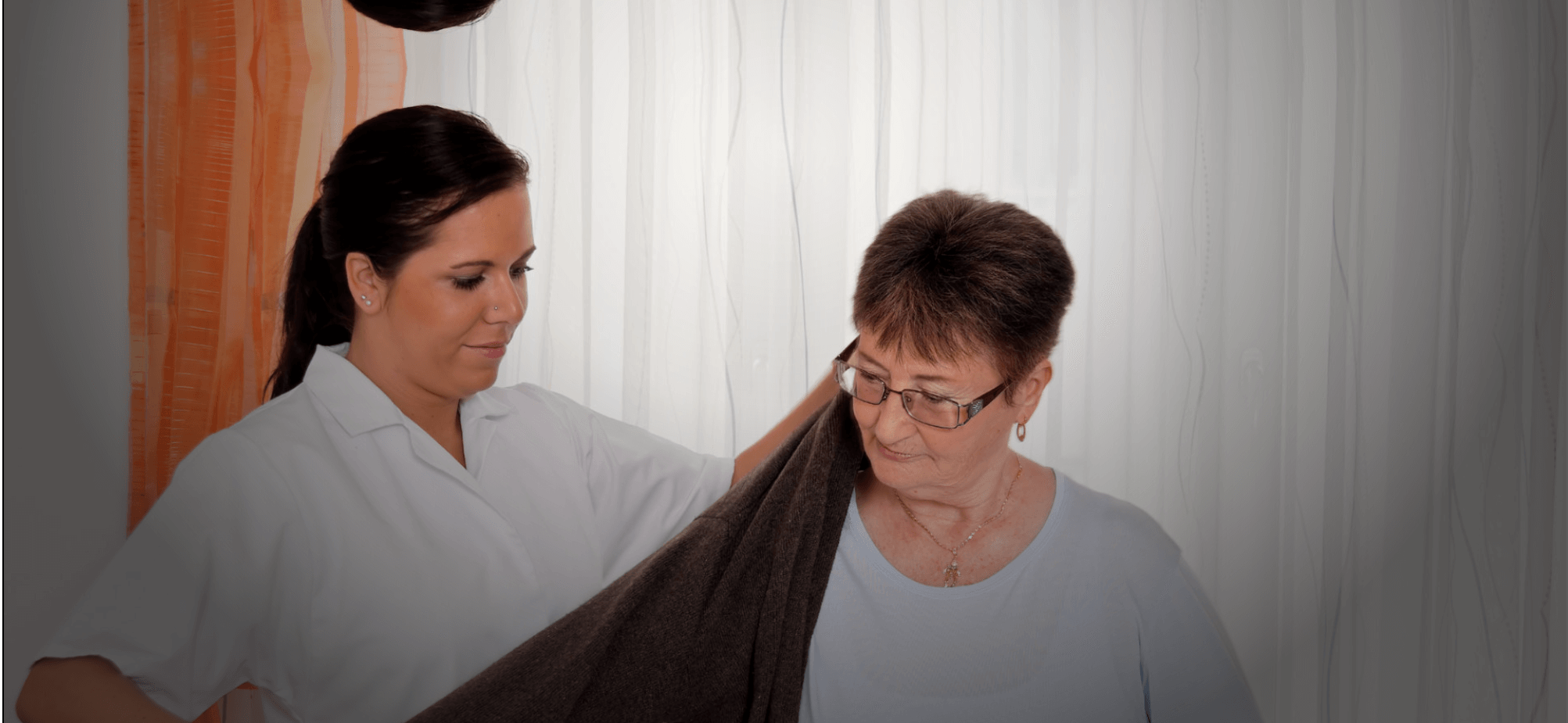a nurse assisting an old woman to dress up
